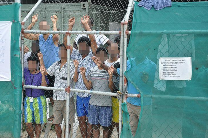Asylum-seekers look through a fence at the Manus Island detention centre in Papua New Guinea
